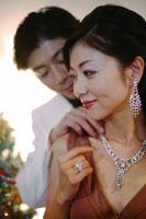 女性の首にネックレスをつける男性