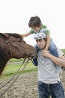 馬と肩車をする親子