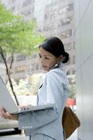 街角でノートパソコンを操作するビジネスウーマン