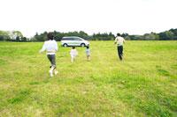 草原で車へ向かって走るファミリー 30700000027| 写真素材・ストックフォト・画像・イラスト素材|アマナイメージズ