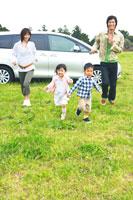 車から降りて草原を走るファミリー 30700000030| 写真素材・ストックフォト・画像・イラスト素材|アマナイメージズ