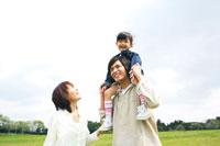 草原で娘を肩車する父と付き添う母