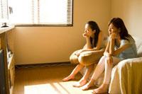 ソファにすわる2人の20代日本人女性