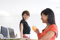 オフィスで話す2人の20代日本人女性 30701000104| 写真素材・ストックフォト・画像・イラスト素材|アマナイメージズ