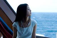 フェリーの窓から海を見る20代日本人女性