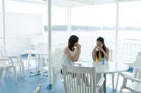 船上カフェでパンを食べる2人の20代日本人女性