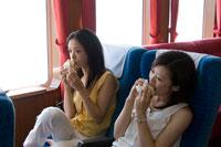 フェリーの中でパンを食べる2人の20代日本人女性