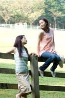 牧場の柵に寄りかかる2人の20代日本人女性