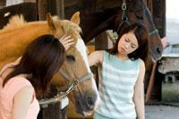 馬をなでる2人の20代日本人女性