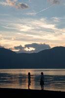 夕暮れの湖畔に立つ2人の20代日本人女性 30701000298| 写真素材・ストックフォト・画像・イラスト素材|アマナイメージズ