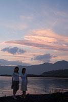 夕暮れの湖畔に立つ2人の20代日本人女性