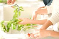 野菜を洗う日本人の女の子2人と父親の手元