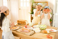 キッチンで料理をする日本人の女の子たち