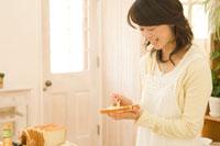 パンにバターを塗る日本人女性