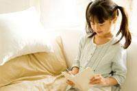 ソファで本を読む日本人の女の子