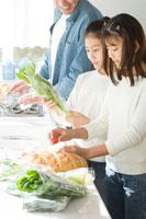 キッチンで料理中の日本人の父親と娘2人