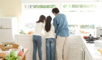 キッチンで料理中の父親と娘2人の背中
