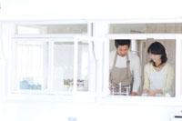 キッチンで洗い物をする日本人の夫婦