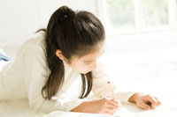 窓際で宿題をする日本人の娘