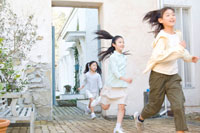 屋外で競争して遊ぶ日本人の娘3人