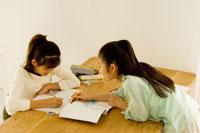 室内のテーブルで宿題をする日本人の娘2人