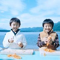 湖畔で野菜の皮を剥く2人の男の子 30702000008| 写真素材・ストックフォト・画像・イラスト素材|アマナイメージズ