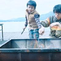 湖畔でBBQ用グリルで薪を焚く父と息子