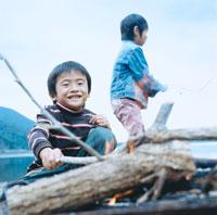 湖畔で焚火をおこす2人の男の子 30702000014| 写真素材・ストックフォト・画像・イラスト素材|アマナイメージズ