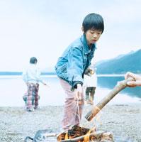 湖畔でおこした焚火のそばで遊ぶ4人の男の子