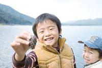 湖畔で松ぼっくりを見つけた2人の男の子