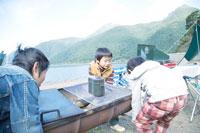 湖畔でBBQ用グリルを運ぶ3人の男の子