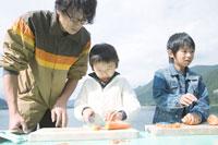 湖畔でニンジンを切る成人男性と2人の男の子 30702000046| 写真素材・ストックフォト・画像・イラスト素材|アマナイメージズ
