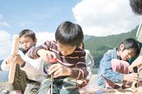 湖畔で木の工作をする4人の男の子