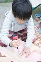 屋外で木の工作をする男の子 30702000058| 写真素材・ストックフォト・画像・イラスト素材|アマナイメージズ
