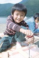 湖畔で木の工作をする男の子