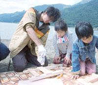 湖畔で木の工作をする成人男性と子供たち