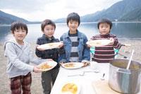 湖畔でカレーライスを持って喜ぶ4人の男の子 30702000074| 写真素材・ストックフォト・画像・イラスト素材|アマナイメージズ