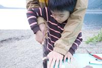 湖畔で木の工作を教わる男の子