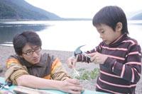湖畔で木の工作をする父と息子 30702000094| 写真素材・ストックフォト・画像・イラスト素材|アマナイメージズ