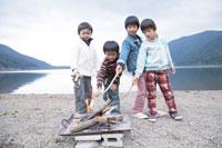 湖畔で焚火をおこす4人の男の子