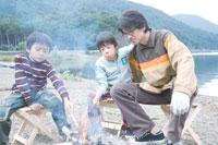 湖畔で焚火をおこす成人男性と2人の男の子 30702000103| 写真素材・ストックフォト・画像・イラスト素材|アマナイメージズ