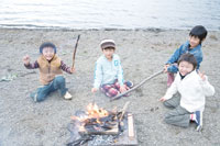 湖畔でおこした焚火を囲む4人の男の子