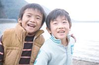 湖畔で肩を組んで笑う2人の男の子 30702000107| 写真素材・ストックフォト・画像・イラスト素材|アマナイメージズ