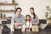女の子を中心にソファーに座る3人家族