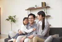 ソファーで笑顔の3人家族