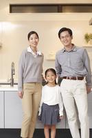 キッチンの前に立つ3人家族