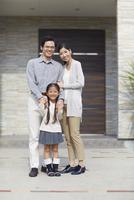 家の前に立つ3人家族