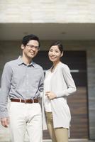 家の前に立つ夫婦
