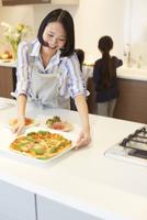 キッチンにピザを置く奥さん