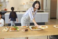 テーブルに食事を用意する親子